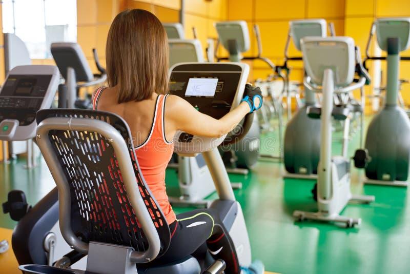 Fotosportkvinnan som sitter på en stationär cykel och att göra den cardio övningen som trampar, mäter pulsen arkivbild