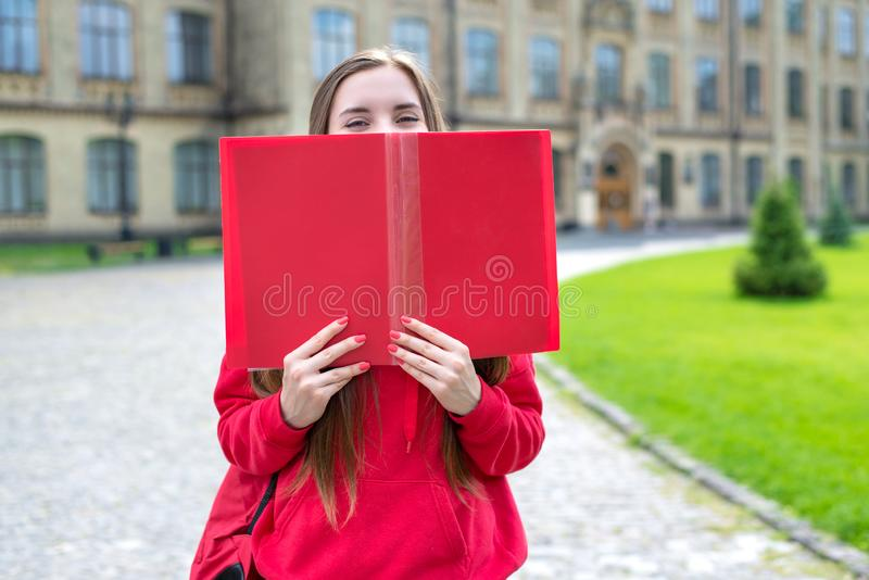 Fotostående av att charma det millennial bokslutet för härlig gladlynt upphetsad tonårig hipster som täcker hennes framsida och l royaltyfria foton