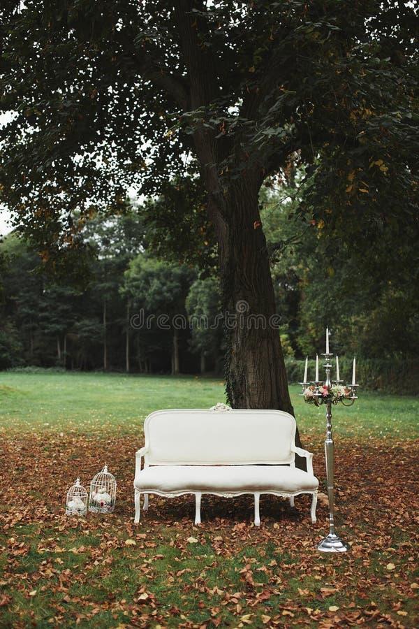 Fotostreek met bank huwelijksdecoratie voor fotospruit klassieke witte bank in de aard kandelaar in het binnenland stock foto's