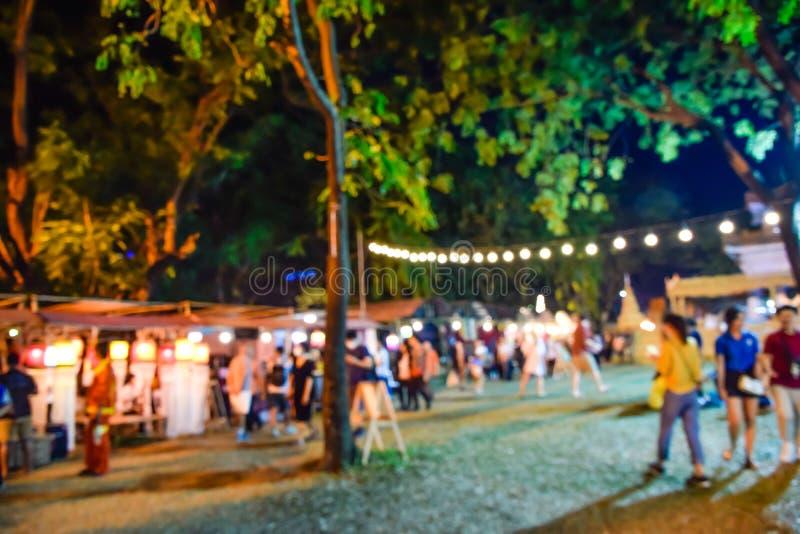 Fotosuddighet - Defocus eller ut ur fokusfolk som går runt om nattturismfestivalen i, parkerar i Bangkok, Thailand, nattmarknad arkivbilder