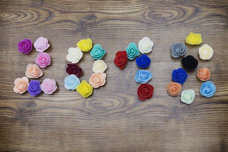 2018, Fotozahldesign mit Blumen tapezieren hölzernen Hintergrund lizenzfreies stockfoto
