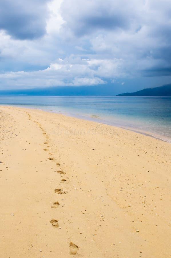 Fotspår i en tropisk strand arkivfoto