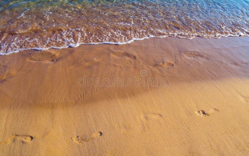 Fotsp?r i sanden p? den tomma sandiga stranden - liten skummande v?g och klart bl?tt vatten arkivbilder