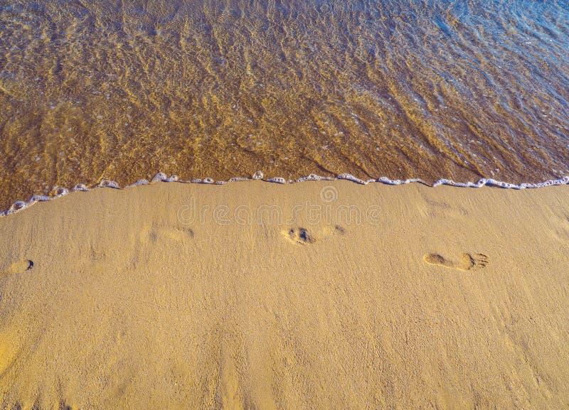 Fotsp?r i sanden p? en tom sandig strand, lugna hav arkivfoto