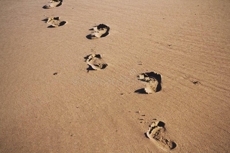 Fotspår i sanden på Polzeath sätter på land det Retro filtret för tappning royaltyfri fotografi