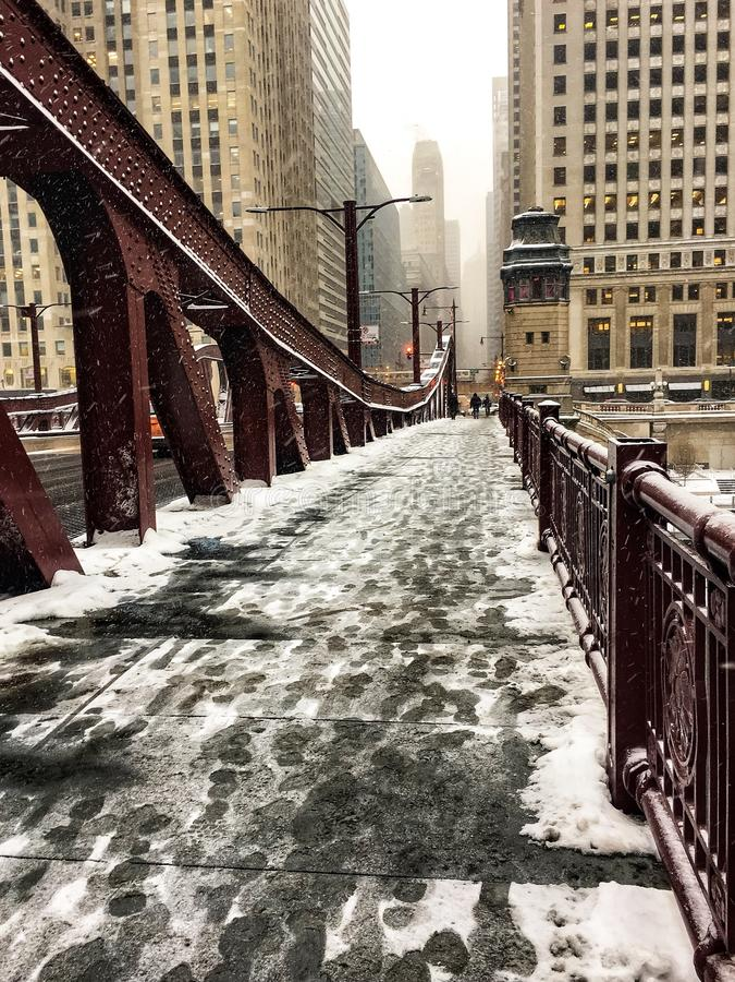Fotspår i snö täckte bron över Chicago River under tungt snöfall arkivfoto