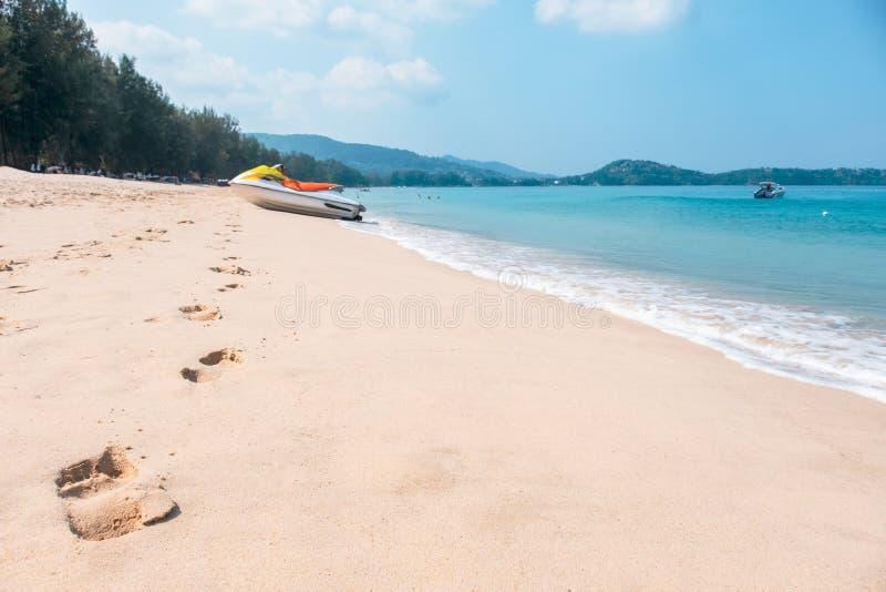 Fotsp?r och havsv?g p? den sandiga stranden med bl? himmel royaltyfria bilder