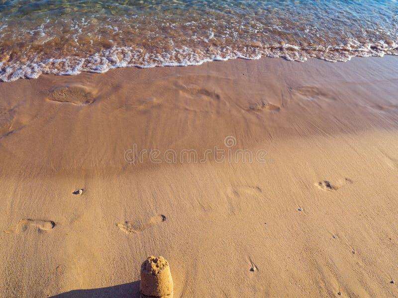 Fotsp?r och liten sandslott p? den tomma stranden - lugna sm? v?gor royaltyfria bilder