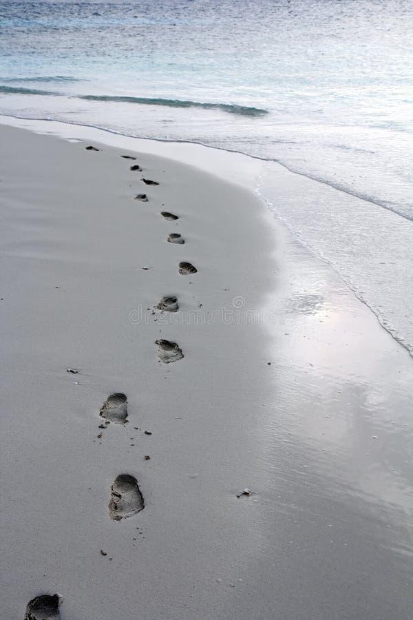 Fotspår på den sandiga stranden arkivfoton