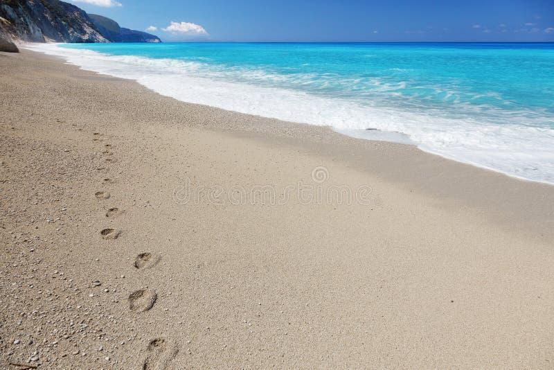 Fotspår på den sandiga stranden arkivbilder