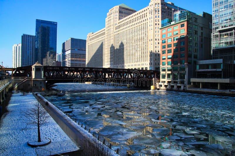Fotspår på entäckt riverwalk tillsammans med ett djupfrysta Chicago River med att sväva isstora bitar arkivbilder