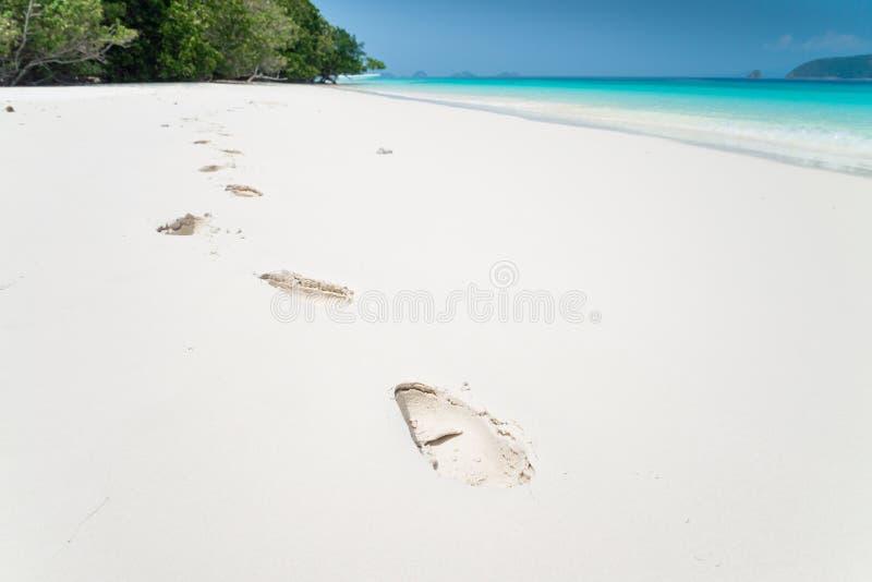 Fotspår på mjuk vit sand för den härliga tropiska ön sätter på land bl arkivbild