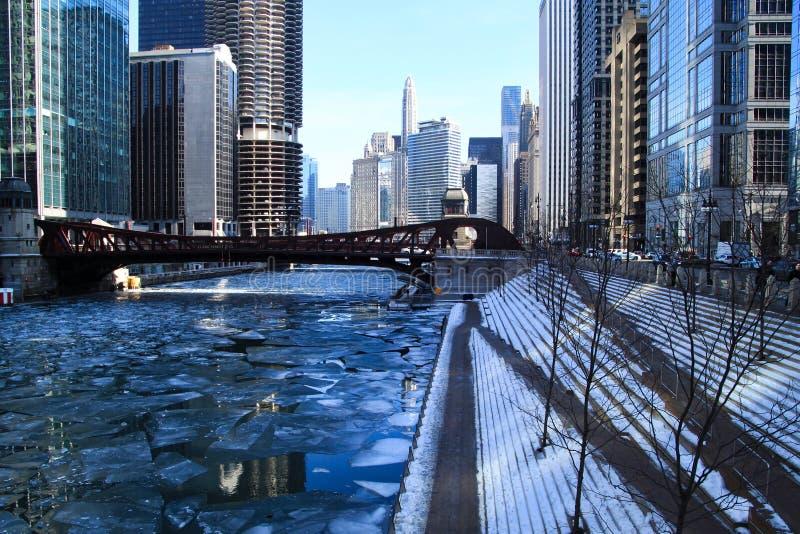 Fotspår på snö-täckte moment som ner leder till ett djupfrysta Chicago River i Januari royaltyfri bild