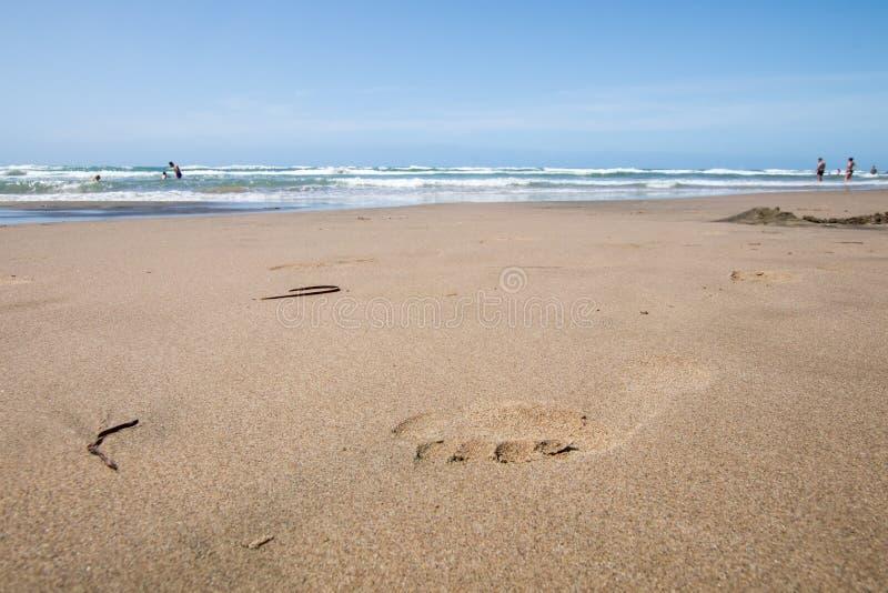 Fotspåret på våt sand, sätter på land simbolic form royaltyfri foto