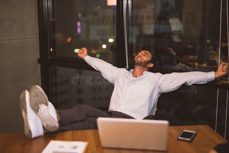 Fotstödet kopplade av säkert ungt affärsmansammanträde med ben på skrivbordet på kontoret royaltyfri fotografi