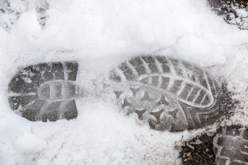 Fottryck av en m?nsklig sko p? den vita sn?n royaltyfri bild