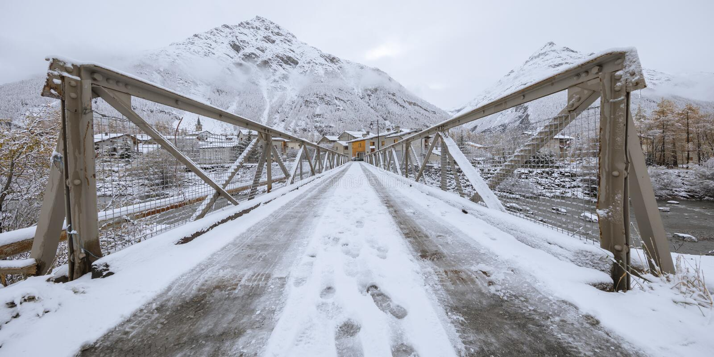 Fottryck i snön på en bro som leder till byn, Bessans, Frankrike 2018 fotografering för bildbyråer