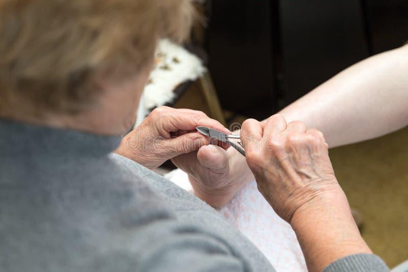 Fotvårdsspecialisten ger en medicinsk behandling hemma royaltyfri fotografi
