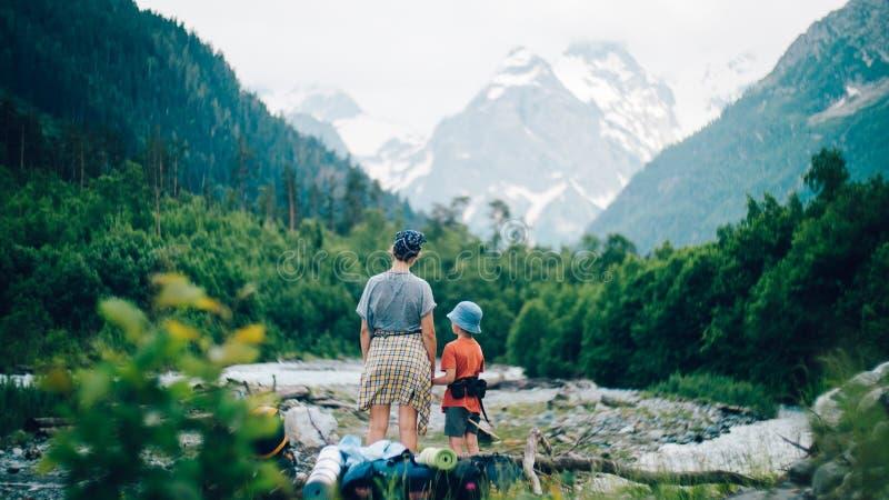 fotvandra berg för familj En ung moder och hennes son fotvandrar tillsammans i bergen på en härlig sommarafton arkivbild