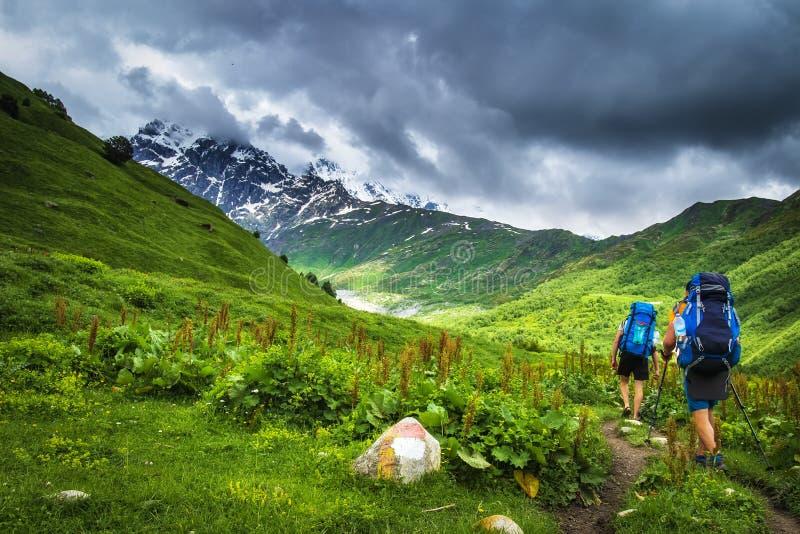 fotvandra berg Turister med ryggsäckar i berg Trekking i den Svaneti regionen, Georgia Vandring för två män i monteringsslinga royaltyfria bilder