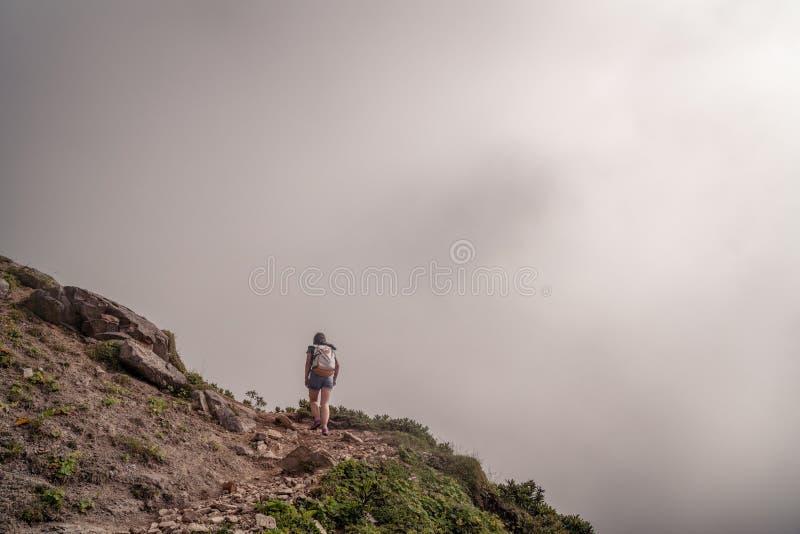 Fotvandra - fotvandrarekvinna på trek med ryggsäcken som bor sund aktiv livsstil Fotvandrareflicka som går på vandring i berg arkivfoton