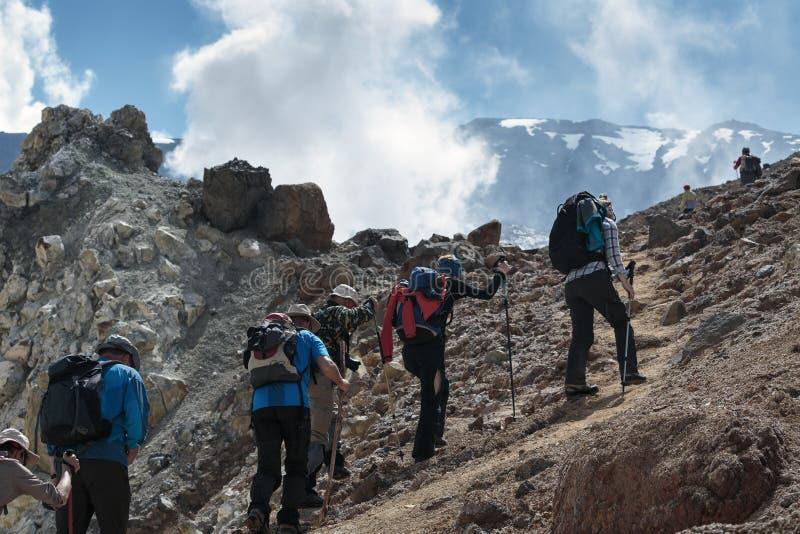 Fotvandra grupp människorklättring till krater av den aktiva vulkan royaltyfria foton