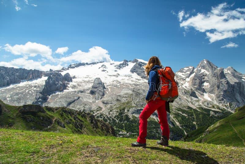 Fotvandra kvinnan i fjällängarna, Dolomites, Italien royaltyfri bild