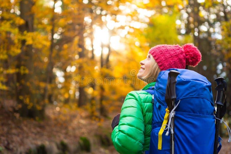 Fotvandra kvinnan med ryggsäcken som ser inspirerande höstgolde arkivbild