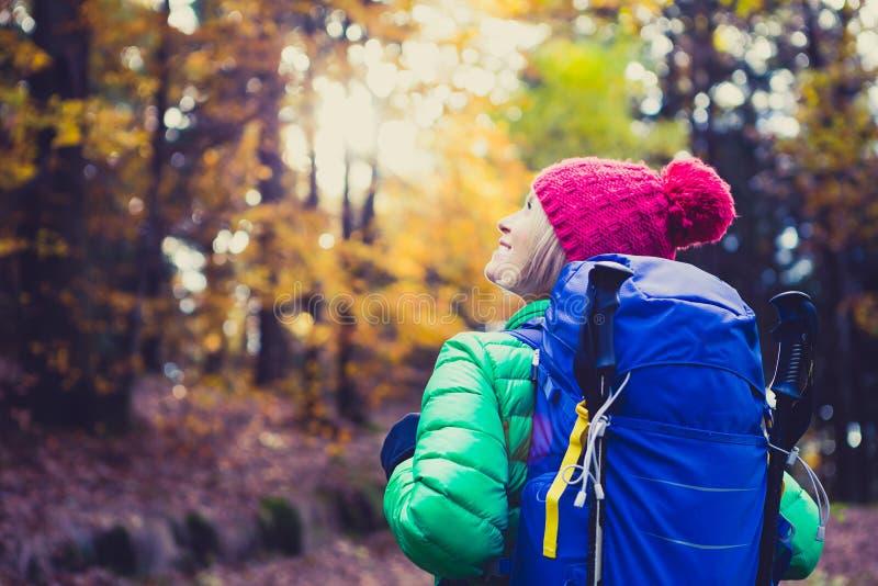 Fotvandra kvinnan med ryggsäcken som ser inspirerande höstgolde arkivfoton