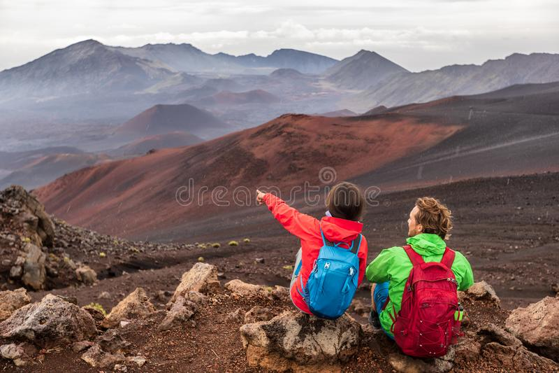 Fotvandra loppsemester i den Maui vulkan, Hawaii USA loppkvinna med ryggsäcken som pekar på det Haleakala vulkanlandskapet Par fotografering för bildbyråer