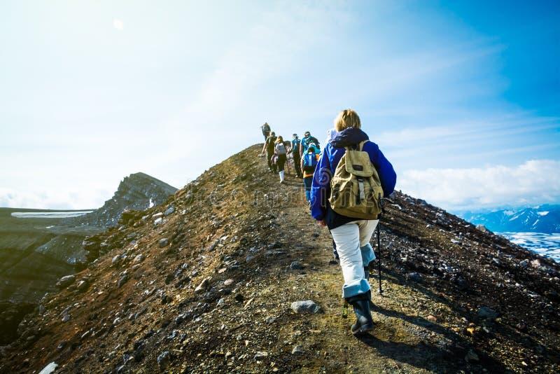 Fotvandra på Kamchatka: gruppen av fotvandraren med ryggsäcken går i mounta arkivbild