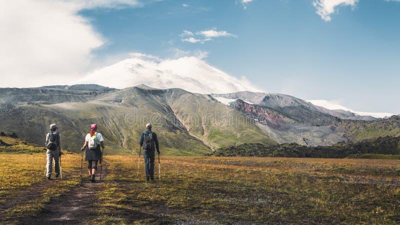 Fotvandra Team Goes To Mount Elbrus, bakre sikt Begrepp för begrepp för livsstil för loppdestinationserfarenhet royaltyfria bilder
