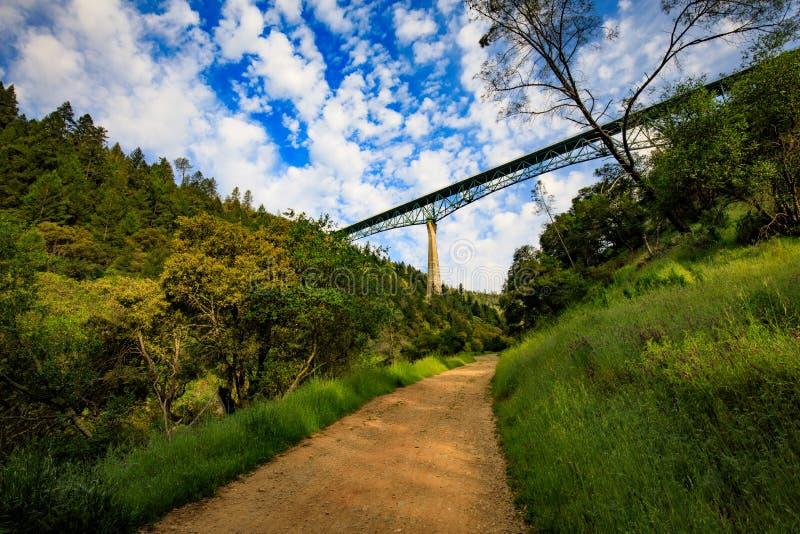 Fotvandra under den Foresthill bron i kastanjebruna Kalifornien, denmest högväxta bron i USA och ställningar över den amerikanska fotografering för bildbyråer