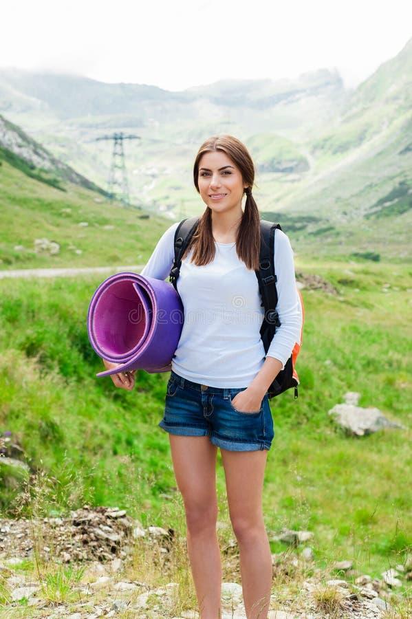 Fotvandrare för ung dam med ryggsäcksammanträde på berget royaltyfri foto