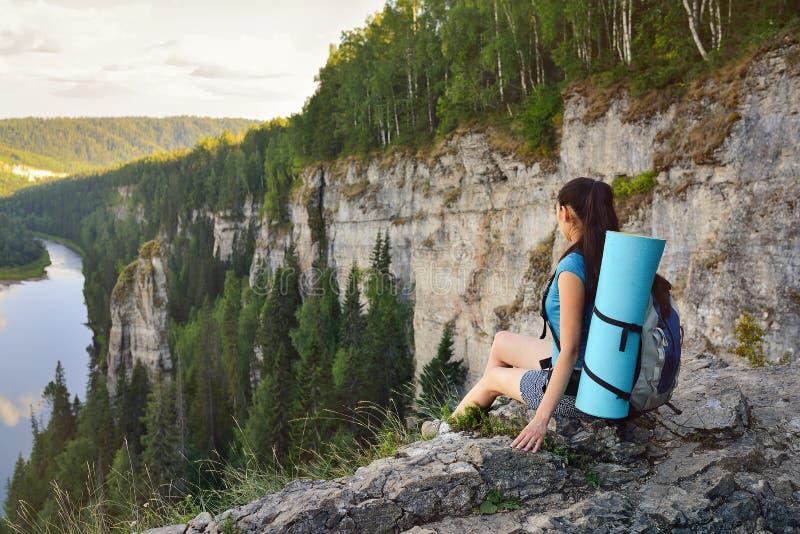 Fotvandrare för ung kvinna med ryggsäcksammanträde på kanten av klippan på hög höjd arkivbilder