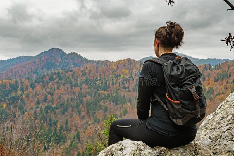 Fotvandrare för ung kvinna som tycker om sikten av det härliga höstliga landskapet arkivfoto