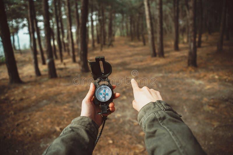 Fotvandrare med kompasset som pekar riktning i skogen arkivfoto
