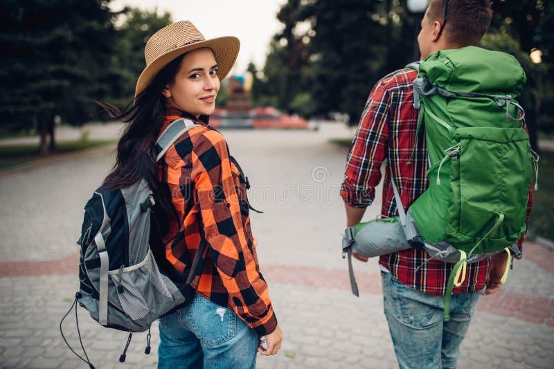 Fotvandrare med ryggsäckar som reser i turist- stad royaltyfria bilder