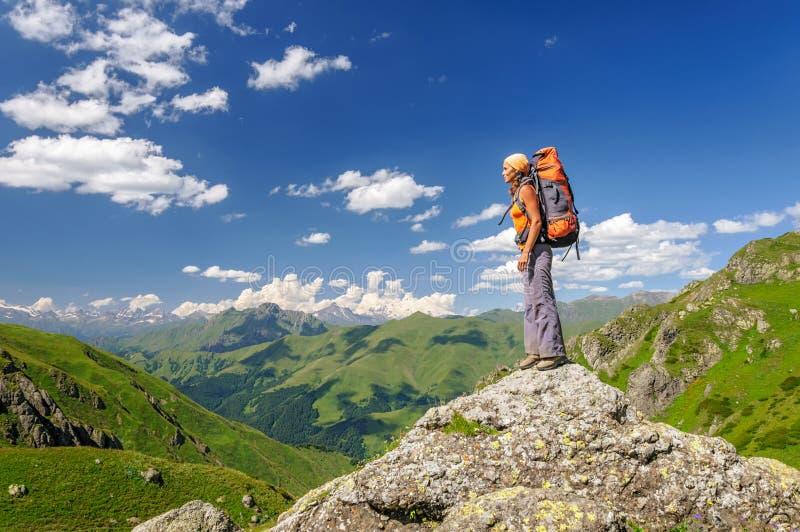 Fotvandrare med ryggsäcken som överst kopplar av av ett berg fotografering för bildbyråer