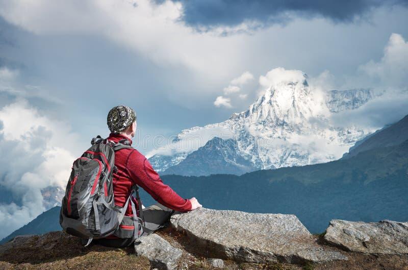 Fotvandrare med ryggsäcken som överst ser av berget under en vandring arkivbild