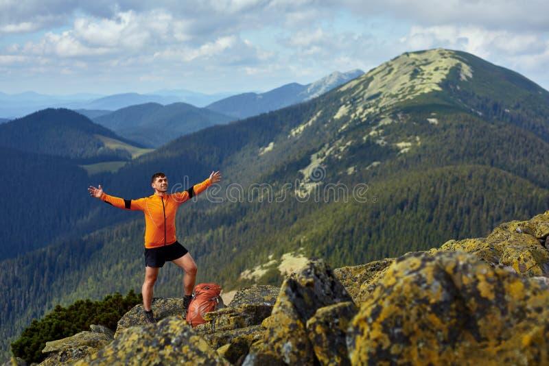 Fotvandrare med ryggsäcken som överst står av ett berg med lyftta händer royaltyfri fotografi