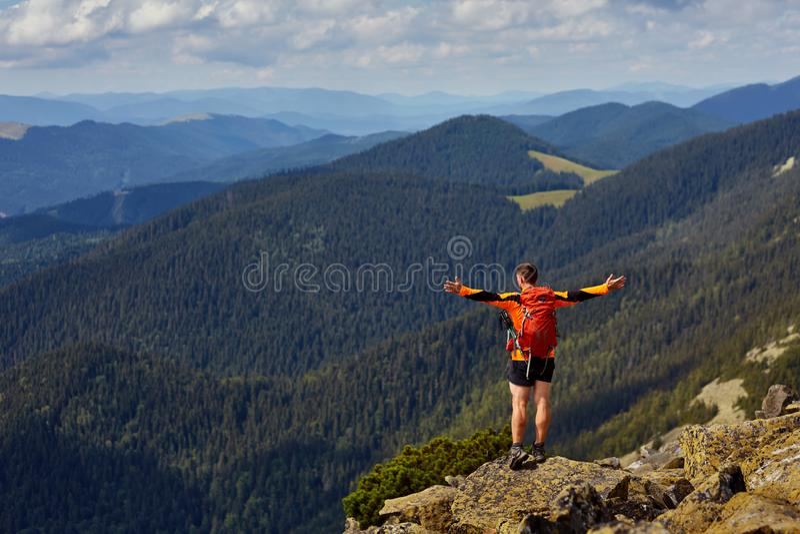 Fotvandrare med ryggsäcken som överst står av ett berg med lyftta händer arkivfoto