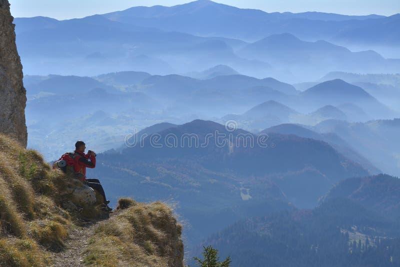 Fotvandrare med ryggsäcksammanträde på klippan av ett berg och att se till och med kikare royaltyfria bilder