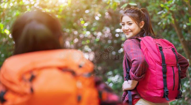 Fotvandrare med ryggs?ckar som g?r till och med en ?ng med frodigt gr?s Ung asiatisk kvinnlig hipster som två fotvandrar på bergf royaltyfri bild