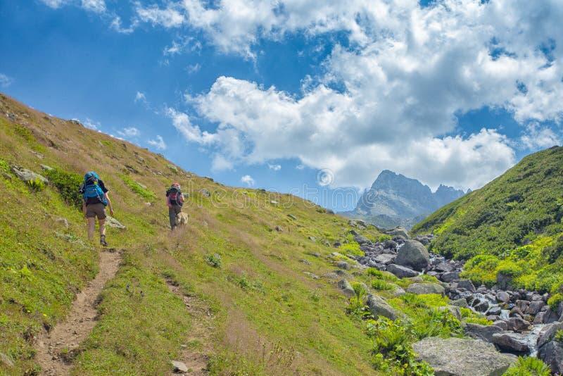fotvandrare med stora ryggsäckar som fotvandrar på berget Kackarlar arkivbild
