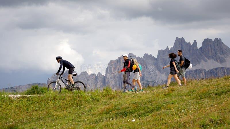 Fotvandrare och cyklist på bergslingan royaltyfri foto