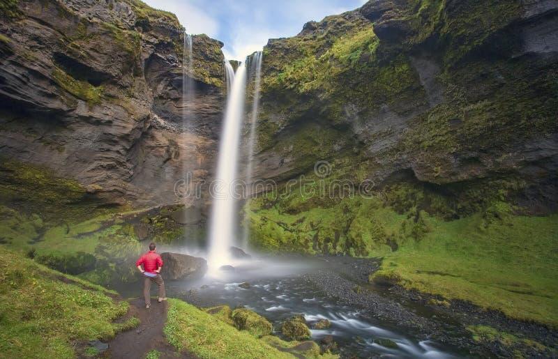 Fotvandrare på den Kvernufoss vattenfallet arkivbilder