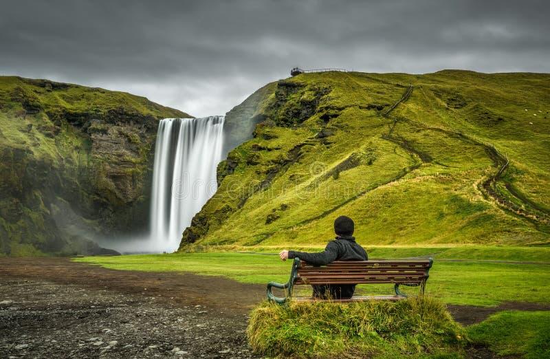 Fotvandrare på den Skogafoss vattenfallet i sydliga Island royaltyfria bilder