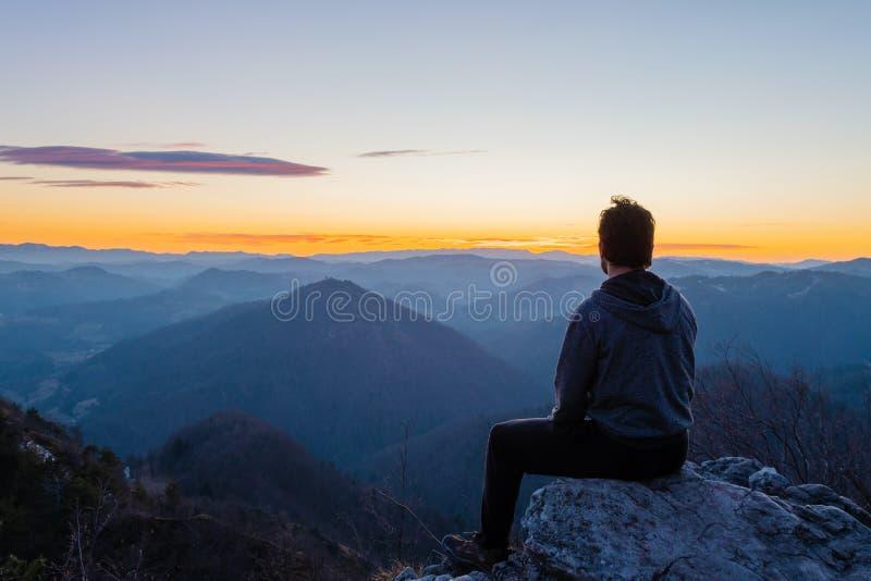 Fotvandrare som överst sitter av den väntande på soluppgången för kulle och tycker om scenisk sikt royaltyfri bild