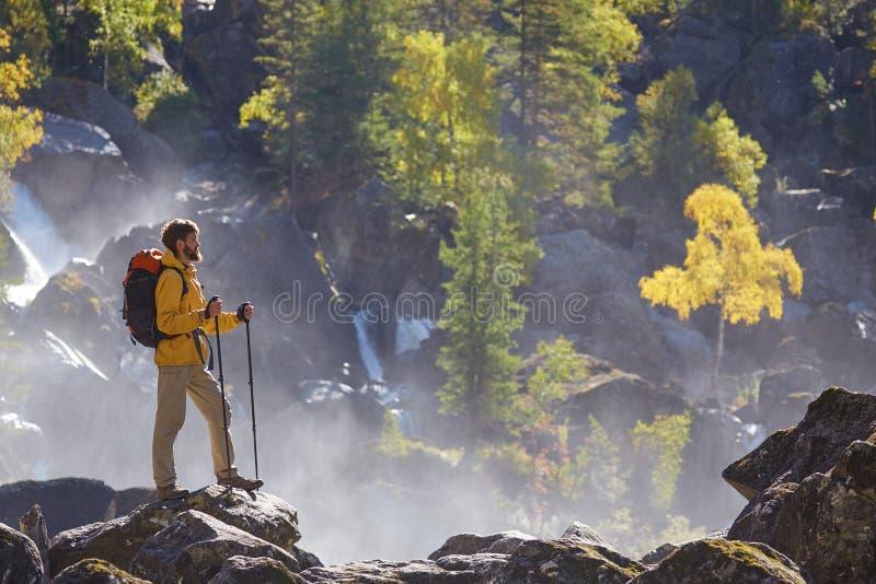 Fotvandrare som fotvandrar med ryggsäcken som ser bergfloden royaltyfri foto